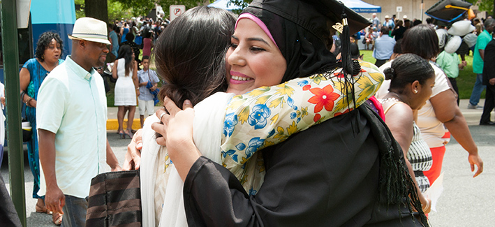 female student graduating and hugging her friend