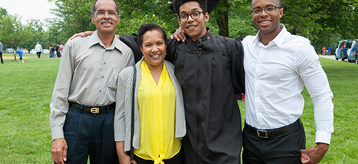 student on commencement day with their family