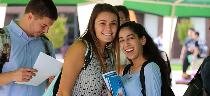 Two young CCBC students smile for a photo under the first week tent