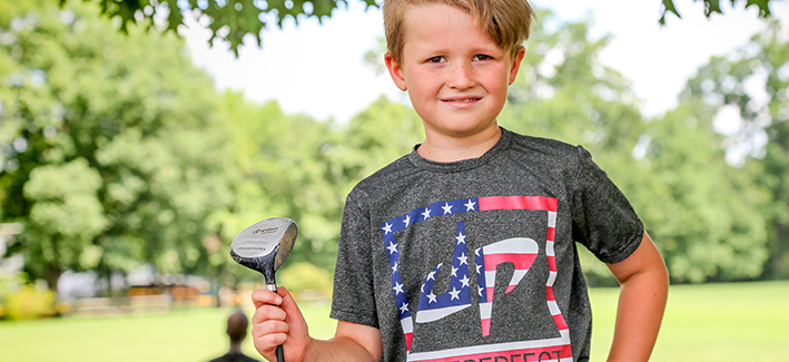 Photo of young boy holding a golf club outside on a sunny day