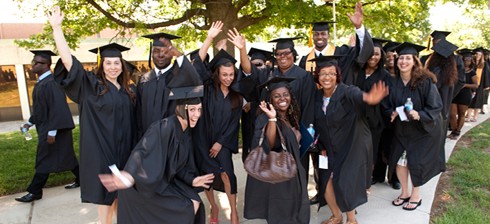 group of students wave excitedly at the camera in cap and gowns