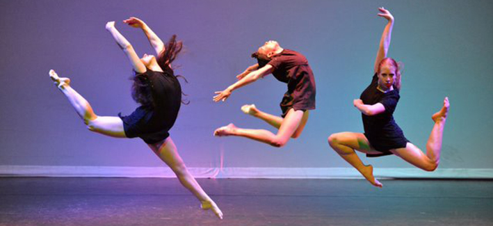 3 students dancing on stage, jumping in the air