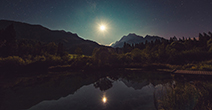 Bright moon reflecting over a lake with mountains in the background