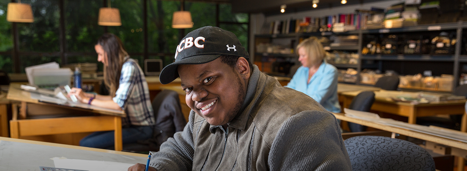 student in the library wearing a ccbc hat