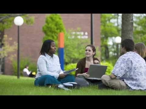 students sitting in a group on the lawn outside having a discussion